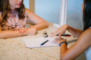 Two women talking over a desk