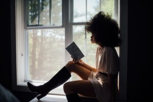 Woman sat on window sill reading