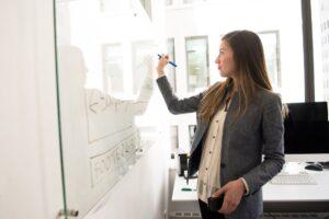 Woman Wearing Gray Blazer Writing on Dry-erase Board
