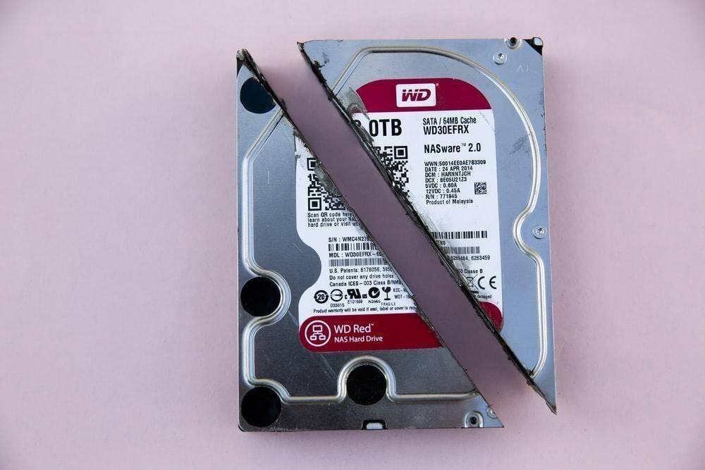 Western Digital WD Red internal HDD sliced in half on pink surface