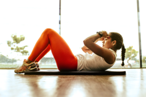 Woman doing crunches in front of a large window