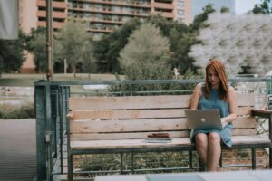 Woman sat on a park bench using a laptop