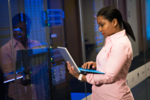 Woman looking at laptop standing in front of a server bank