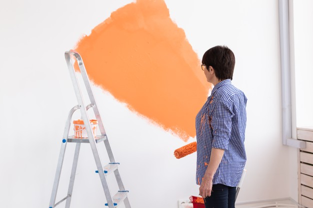 Pretty smiling middle-aged woman painting interior wall of home with paint roller.
