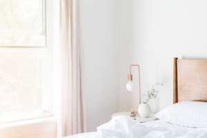 White table lamp and a vase on a nightstand