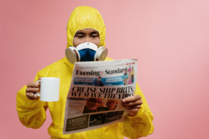 Man in safety gear reading a newspaper and drinking a coffee