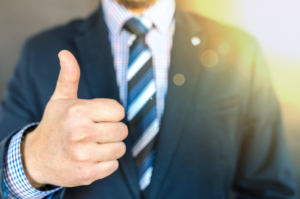Man in suit and tie giing a thumbs up
