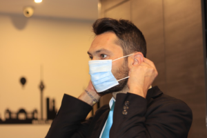 Man wearing a suit putting on a protective face mask