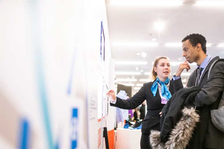 Woman pointing at a board standing next to a collegue