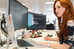 Woman working on triple screen laptop