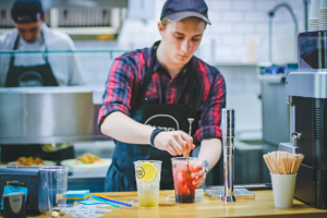 Worker in a restaurant making a drink