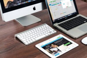 Macbook, iPad and iMac on a wooden desk