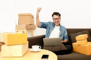 Man surrounded by moving boxes fist pumping