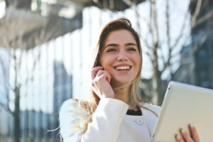 Smiling woman an a phone, holding a tablet
