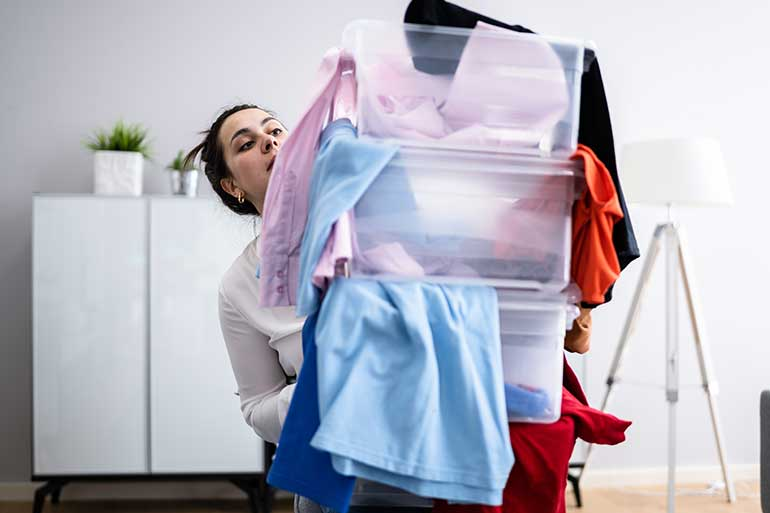 WOman struggling with a pile of storage boxes