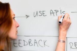 "Woman writing ""Use APIs"" on a whiteboard"