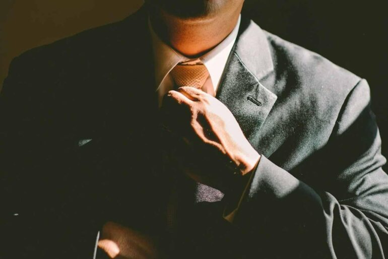 Businessman in a suit adjusting a tie