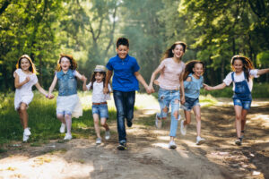 Group of children running down a wooded path