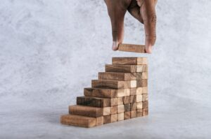 Person stacking small wooden blocks showing growth