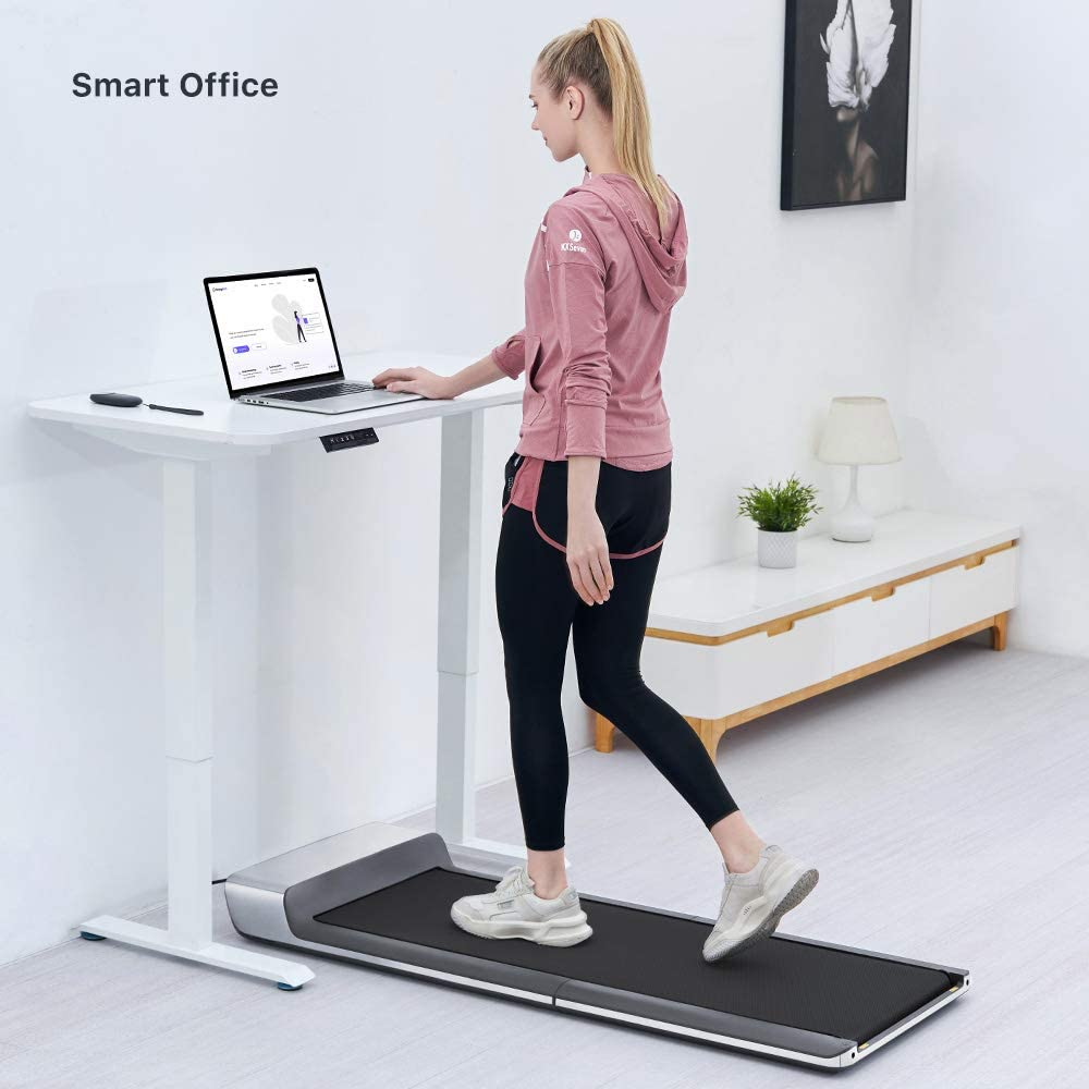Woman using treadmill while working at a standing desk