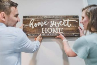 """Couple hanging a sign that says """"Home sweet home"""""""