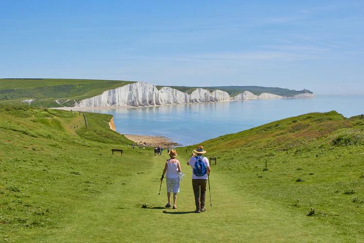Couple walking down a path towards white cliffs