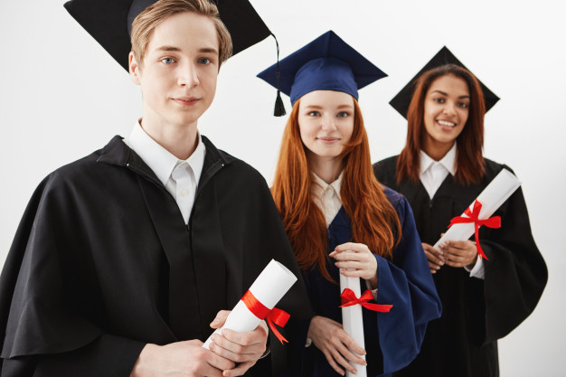 Graduates in their gowns holding diplomas