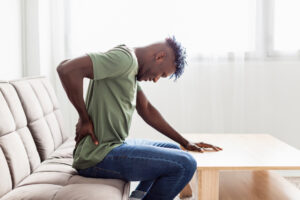 Man sitting on a sofa in pain, rubbing his back