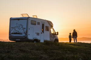 Family watching the sunset by their motor home