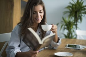 A woman drinking tea while reading a book