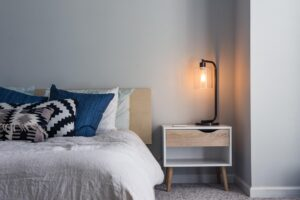 Bed with throw pillows on it and a bedside table with statement lamp