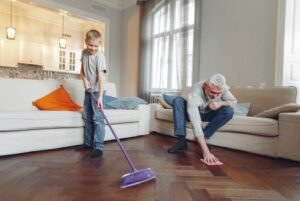Child and man cleaning wooden floor