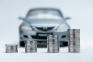 Pile of coins in front of a car