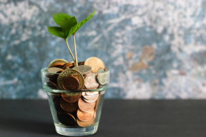Glass full of coins with a plant growing from it