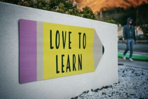 """""""Love to learn"""" pencil shaped sign by the side of a path"""