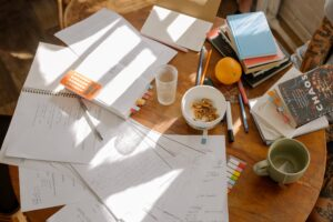 Papers on a desk along with books and cereal