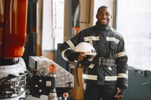 Smiling firefighter holding their helmet