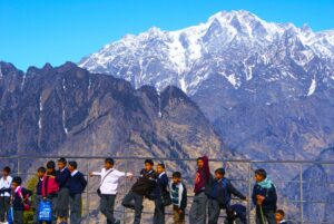 School children standing in front of a scenic mountain