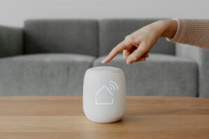 Person pressing on a smart home speaker