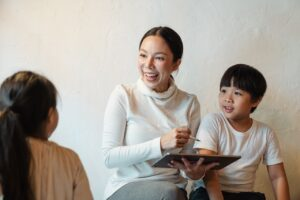 Smiling woman holding a tablet and teaching two children