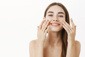 Smiling woman touching her face