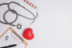 Stethoscope, clipboard, red toy heart and a blister pack of pills