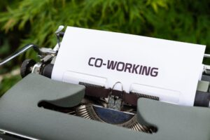 """The word """"Co-working"""" written on paper inserted into a typewriter"""