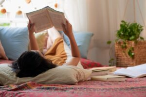 Woman laying on her back in bed reading a book